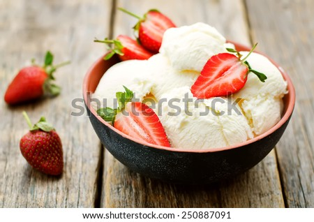 vanilla ice cream with strawberries on a dark wood background. tinting. selective focus - stock photo