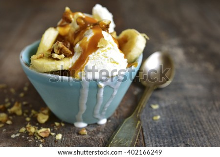 Vanilla ice cream with walnuts,banana and caramel in a blue bowl on a rustic wooden background. - stock photo