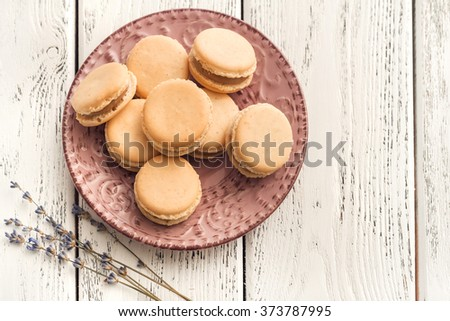 vanilla macaroons with lavender cream on white wooden background - stock photo