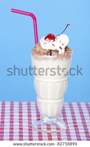 Vanilla milkshake with chocolate creme on a table - stock photo
