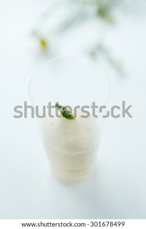 Vanilla mousse in a shot glass garnished with mint leaf. Simple dessert for a garden party or a wedding. Natural back light, shallow depth of field.  - stock photo