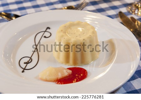 Vanilla mousse  la carte dessert with raspberry sauce pineapple and ornate chocolate decoration - stock photo