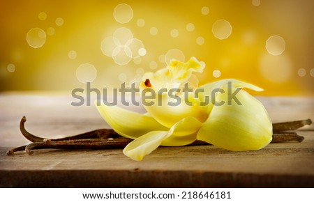Vanilla. Pods and Flower of vanilla over Wooden Background. Vanilla Pod Stick  - stock photo
