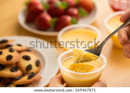 Vanilla Pudding (Egg Custard) taken with a spoon with raisin cookies and fresh strawberries on background - stock photo