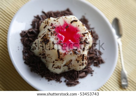 Vanilla pudding with red syrup and chopped chocolate - stock photo