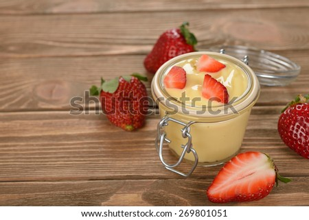 Vanilla pudding with strawberries on a brown background - stock photo
