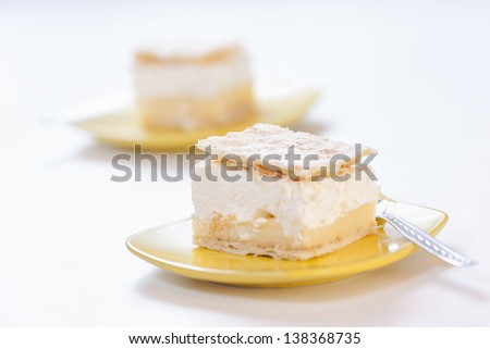 Vanilla slice with puff pastry on top of it, served on a yellow plate. - stock photo