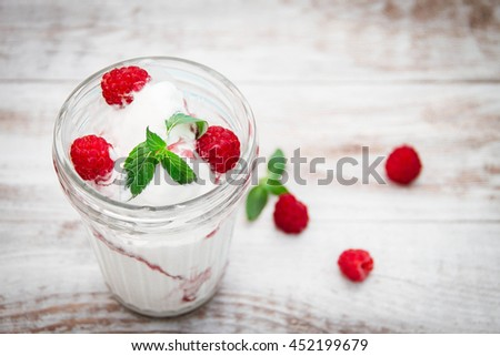 Vanilla sundae ice cream with sauce and raspberry