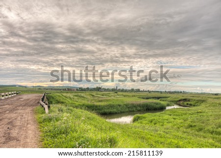 Vanishing dirty road to village with bridge and river valley before against cloudy sky background. Derevni, Yaroslavsky region, Russia.
