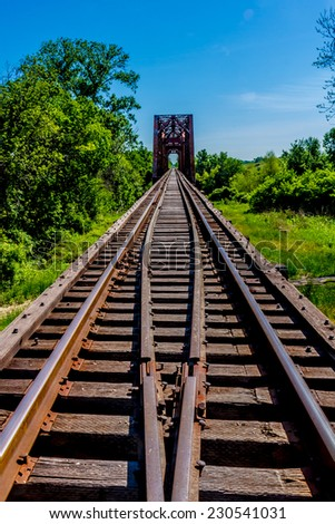 Vanishing Point View of an Old Railroad Trestle with an Old Iconic Iron Truss Bridge Over the Brazos River, Texas. - stock photo