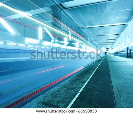 vanishing train arriving on blue metro station with red lines - stock photo