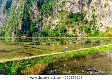 VANLONG NATURAL RESORT, NINHBINH, VIETNAM - NOVEMBER 23, 2014 - An  unidentified man fishing on the lagoon. The local people make use of the lagoon to earn their living by fishing & capturing crabs.  - stock photo