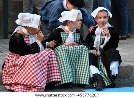 VANNES, FRANCE - AUGUST 15, 2012: Three girls wearing traditional breton costumes and embroidered lace hats participate celtic festival in Vannes, french Brittany on the 15th August 2012.