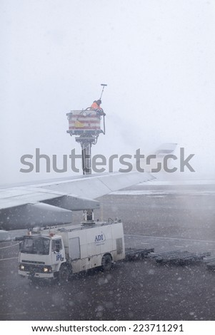 VANTAA AIRPORT, HELSINKI, FINLAND - CIRCA APRIL, 2013: Process of aircraft wings defrosting with antifreeze before takeoff during strong blizzard. Services of large Finland airport - stock photo