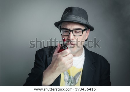 Vaping man looks at his e-cigarette with a puzzled expression.