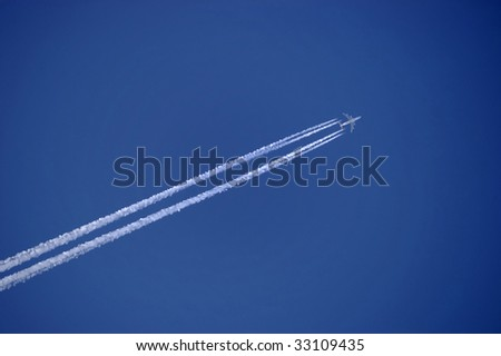 vapor trail from an airplane against clear blue sky - stock photo