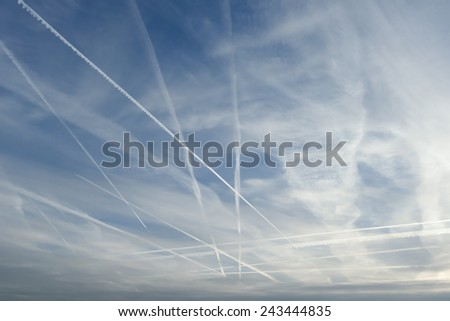 Vapor trails against blue afternoon sky - stock photo