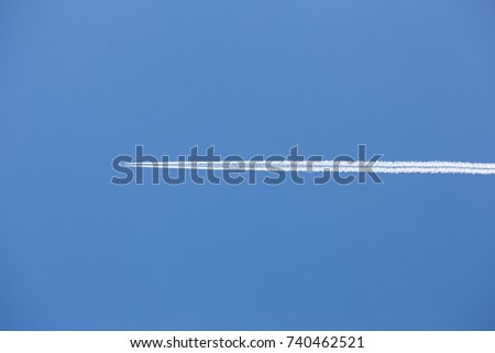 vapour trail behind an airplane on a clear blue day