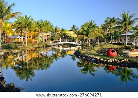 Varadero, Cuba Bungalows of hotel in territory with palm trees, river and a bridge. - stock photo
