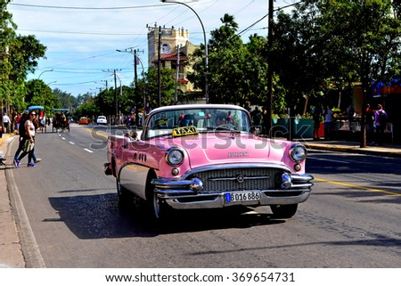 VARADERO, CUBA - JANUARY 18, 2016:  Taxi Driver drives his vintage Buick down the main street in Varadero.  Cuba has many vintage cars and horse drawn carriages being used as taxis. - stock photo