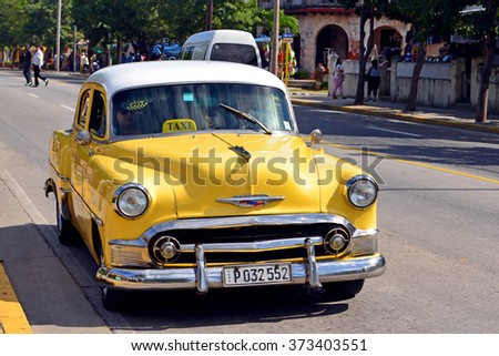 VARADERO, CUBA - JANUARY 18, 2016:  Taxi Driver drives his vintage Chevrolet down the main street in Varadero Cuba.  Cuba has many vintage cars being used as taxis. - stock photo