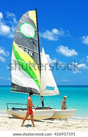 VARADERO, CUBA - May 13, 2016: Happy tourist walking on a  beach around the boat. After more then five decades of restriction American tourist now can visit Cuba - stock photo