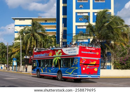 VARADERO - FEB 10: Colorful double-decker tourist bus in front of two hotels on the main street in Varadero, Cuba on Feb. 10, 2015 - stock photo
