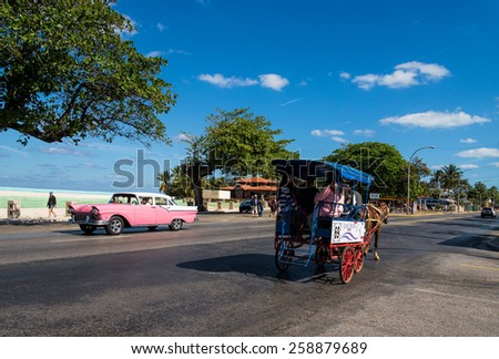 VARADERO - FEB 15: Vintage american car and a horse-drawn carriage transporting locals and tourists on a main street in Varadero, Cuba on Feb. 15, 2015 - stock photo