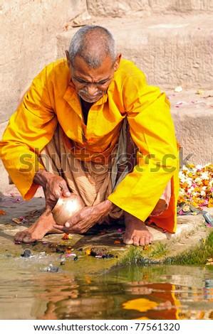 VARANASI, INDIA - APRIL 2: An unidentified Hindu priest cleans prayer utensil with holy water of river Ganges on the morning of Ramnavani on April 2, 2011 in Varanasi, Uttar Pradesh, India - stock photo