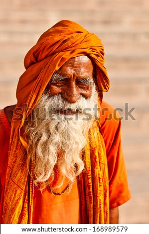 VARANASI, INDIA - APRIL 24: Shaiva sadhu seeks alms on the street on April 24, 2011 in Varanasi, State of Uttar Pradesh, India. Sadhus are holy men who have chosen to live an ascetic life.