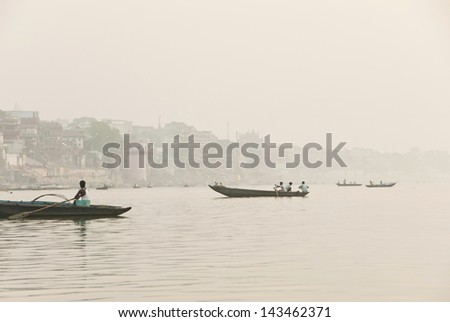 VARANASI, INDIA - APRIL 30: Unidentified Indian fishermen go fishing on the River Ganges in Varanasi, India on April 30, 2009. For most of dwellers fish is main source of livelihood. - stock photo