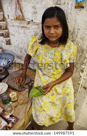 "VARANASI, INDIA - APRIL 30: Unidentified Indian girl prepares for sale ""paan"" on April 30, 2009, Varanasi, India. Paan is a legal (in India) preparation of betel leaf combined with areca or tobacco.  - stock photo"