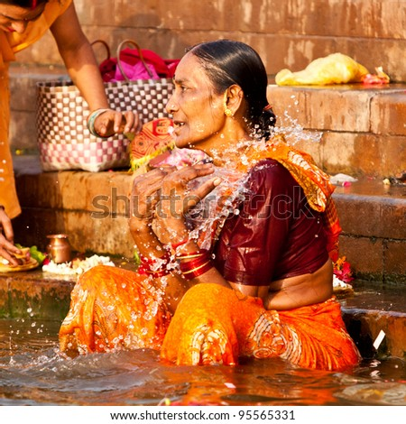 VARANASI, INDIA - APRIL 25: Unidentified woman washes herself in the river Ganga on April 25, 2011 in the holy city of Varanasi, India. The holy ritual of washing is held every day.