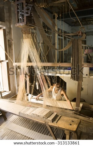 VARANASI, INDIA, DEC 9: Unidentified man makes a traditional sari cloth, hand loom on old fabric factory on Dec 9, 2013, Varanasi, India. Textile industry in Varanasi preserved ancient traditions - stock photo