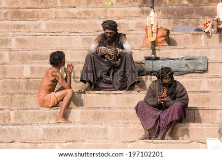 VARANASI, INDIA - DECEMBER 1, 2012 : An unidentified sadhu sits on the ghat along the Ganges river. Tourism has drawn many alleged fake sadhus to Varanasi