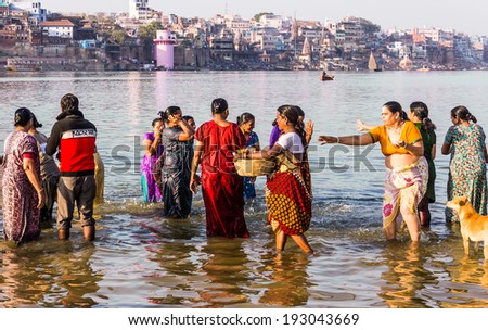 VARANASI, INDIA - FEBRUARY 19, 2014: a group of women taking a holy bath in the river Ganges