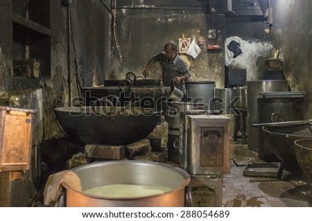 VARANASI, INDIA - 19 FEBRUARY 2015: Indian cook makes last meal after long work day. - stock photo