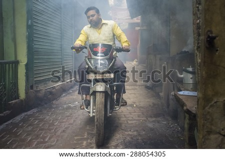 VARANASI, INDIA - 20 FEBRUARY 2015: Man on motorcycle passes through street filled with smoke. Coal ovens are used as source of heat for making milky tea. - stock photo