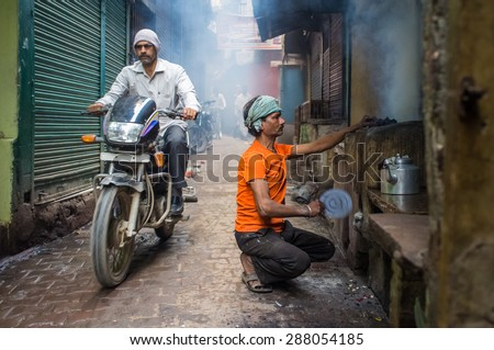 VARANASI, INDIA - 20 FEBRUARY 2015: Street vendor makes fire for milky tea in coal oven while motorcyclist passes by. - stock photo