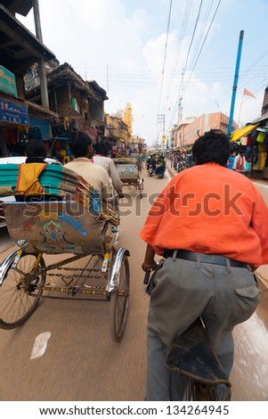 VARANASI, INDIA - JANUARY 27, 2008: An unidentified cycle rickshaw, a standard form of Indian transportation, takes passengers to their destination on January 27, 2008 in Varanasi, India - stock photo