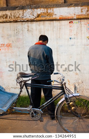 VARANASI, INDIA - JANUARY 26, 2008: An unidentified cycle rickshaw man urinates against a wall in public on January 26, 2008 in Varanasi, India. Public urination is a major social issue in India - stock photo