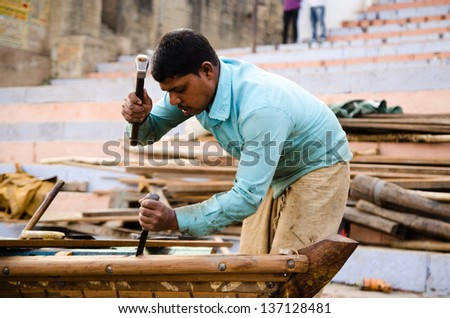 VARANASI, INDIA - 27 JANUARY: Carpenter building boat on 27 January 2013 in Varanasi. Boat trips are one of the most popular tourist activities in Varanasi.