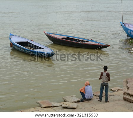 Varanasi, India - Jul 12, 2015. Indian men waiting for tourists taking the boat tour on the sacred Ganges river in Varanasi, Uttar Pradesh, India.