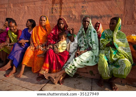 VARANASI, INDIA - JULY 22: Group of Indian women in colorful saris sit and watch the solar eclipse from the banks of the Ganges River July 22, 2009 in Varanasi, India.
