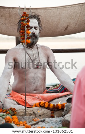 VARANASI, INDIA - MARCH 10: A hindu saint meditates during rituals of Lord Shiva prayer on the auspicious Maha Shivaratri festival on March 10, 2013 at Varanasi, Uttar Pradesh, India. - stock photo