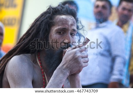 VARANASI - INDIA - 10 MARCH 2013 : A unidentified sadhu is smoking ganja (marihuana) with chillum at the Ghat of Ganges on 10 March 2013 in Varanasi, India.
