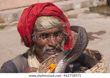 VARANASI, INDIA- 9 MARCH 2013 : unidentified snake charmer enchanting cobras on ghat of Varanasi, People practice this dangerous job as a way of begging charity.
