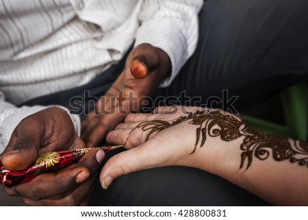 VARANASI , INDIA-  NOVEMBER 13, 2012: indian street  master uses  henna paste or mehndi application on white  tourist woman hand. Traditional Indian natural skin decoration, bio-tattoo