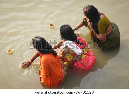 VARANASI, INDIA - NOVEMBER 6: Unidentified people wash themselves in the river Ganga on Nov. 6, 2010 in the holy city of Varanasi, India. The holy ritual of washing is held every day. - stock photo