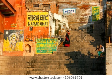 VARANASI, INDIA - SEPTEMBER 9 - Indian woman sweeps steps of Narad Ghat after ceremony of daily morning bathing in the Ganges River on September 9, 2011 in Varanasi, India. - stock photo